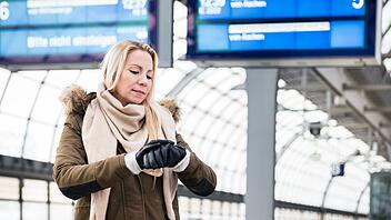Woman looking at wristwatch in train station as her train has a delay