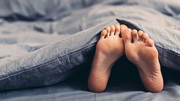 Female beautiful feet under blanket in bed