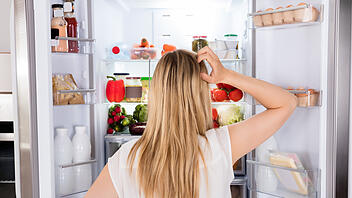 Rear View Of Woman Looking In Fridge
